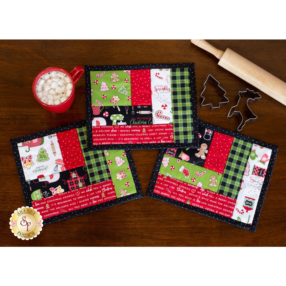 Three mug mats on a wood table with cookie cutters, hot cocoa, and a rolling pin | Shabby Fabrics