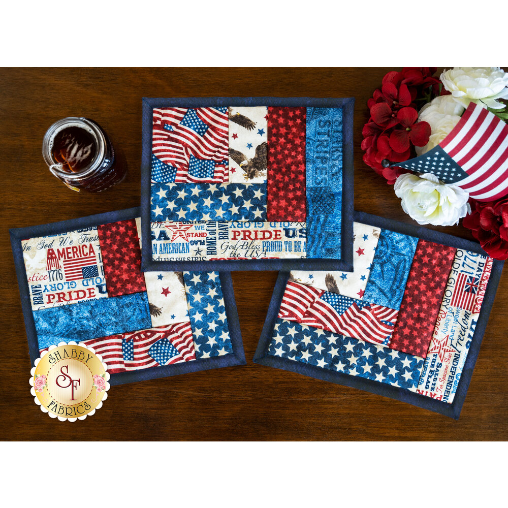 A collection of beautiful patriotic mug mats styled on a wood table with flowers | Shabby Fabrics
