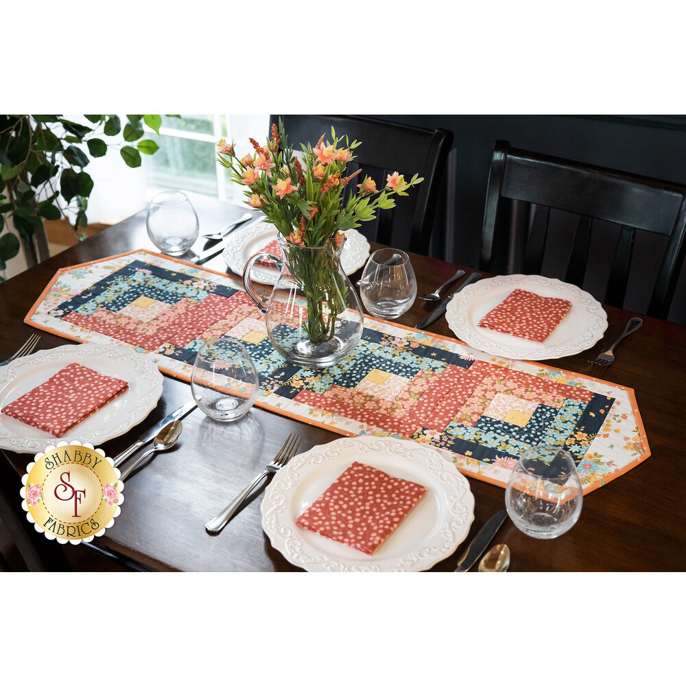 A dark brown table set with Sunlit Blooms projects including the Sunlit Blooms Log Cabin Runner