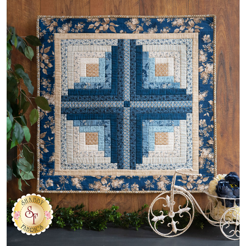 Geometric blue, white, and tan wall hanging displayed on a wall