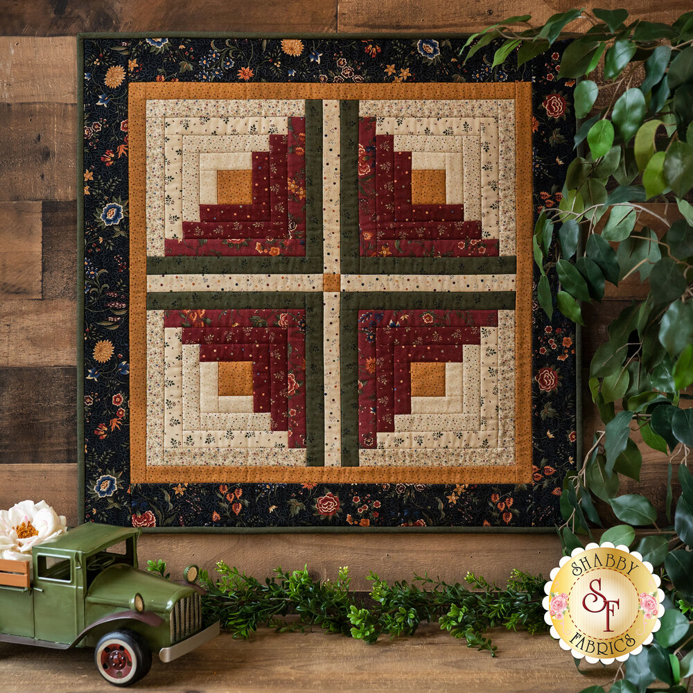 The beautiful Prairie Dreams Log Cabin Wall Hanging displayed on a wall