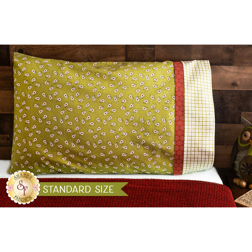 Bright green pillowcase with monkeys and a fun accent stripe resting on a bed