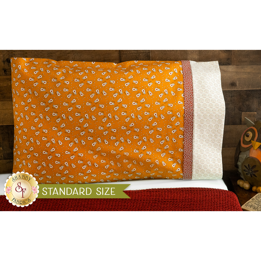Bright orange pillowcase with monkeys and a fun accent stripe resting on a bed