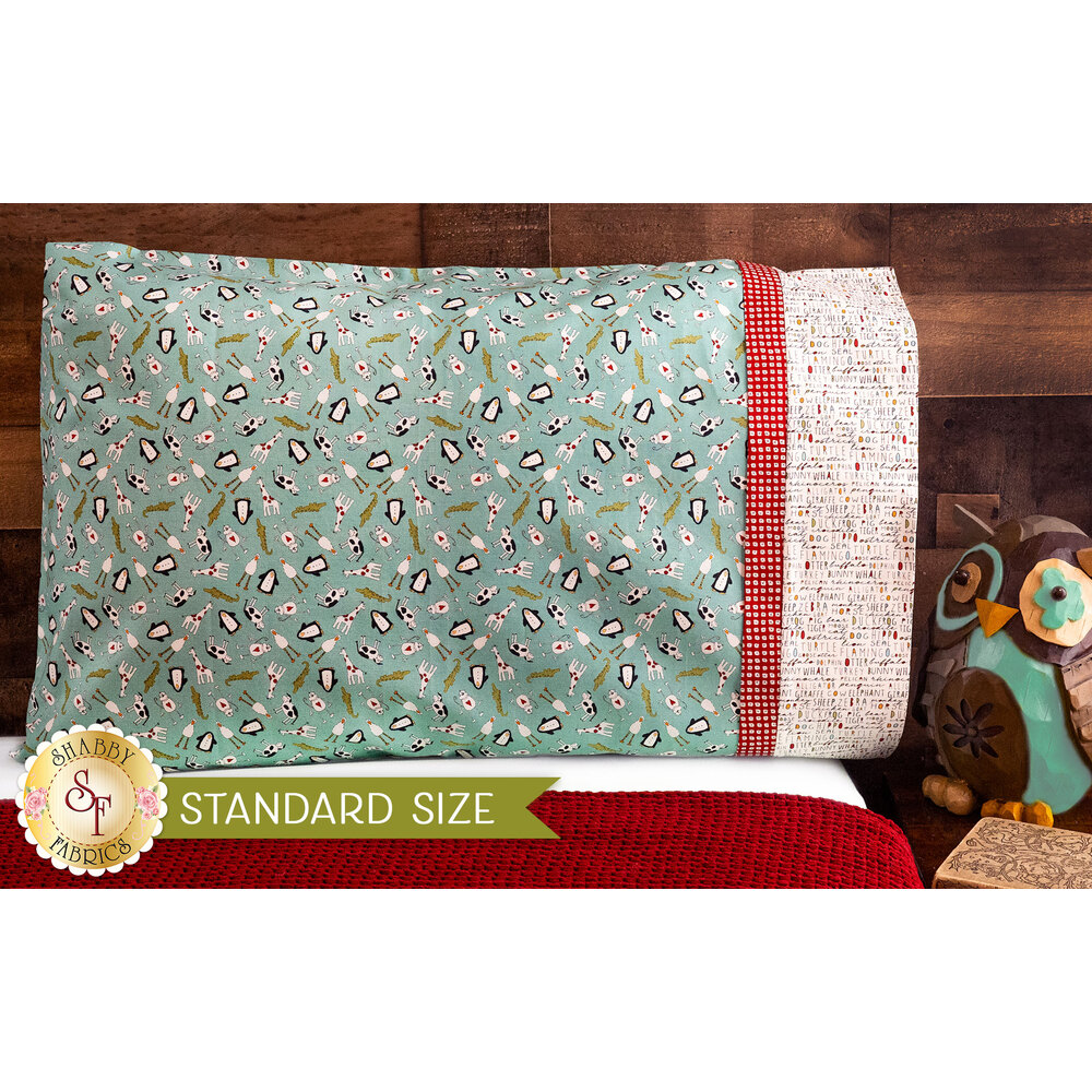A teal, white, and red pillowcase with alligators, penguins and birds resting on a bed