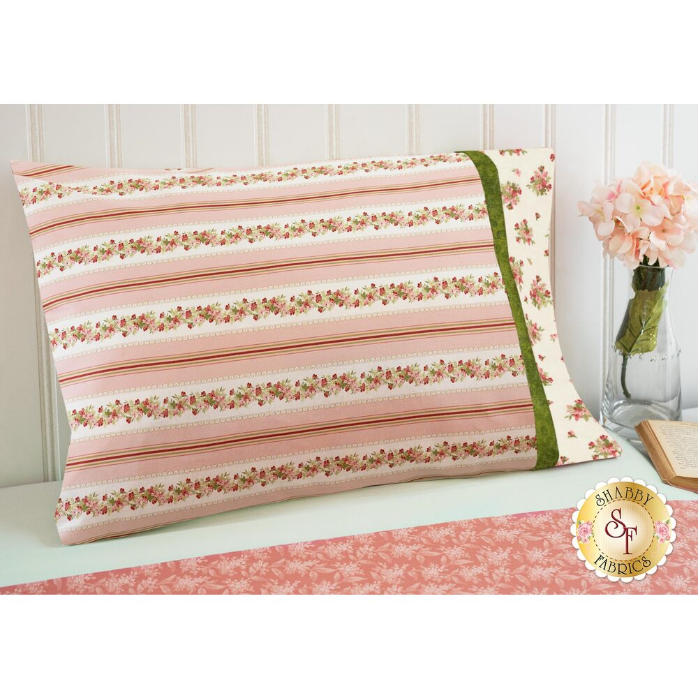 The gorgeous Sensibility Magic Pillowcase - Standard Size in Pink displayed on a bed