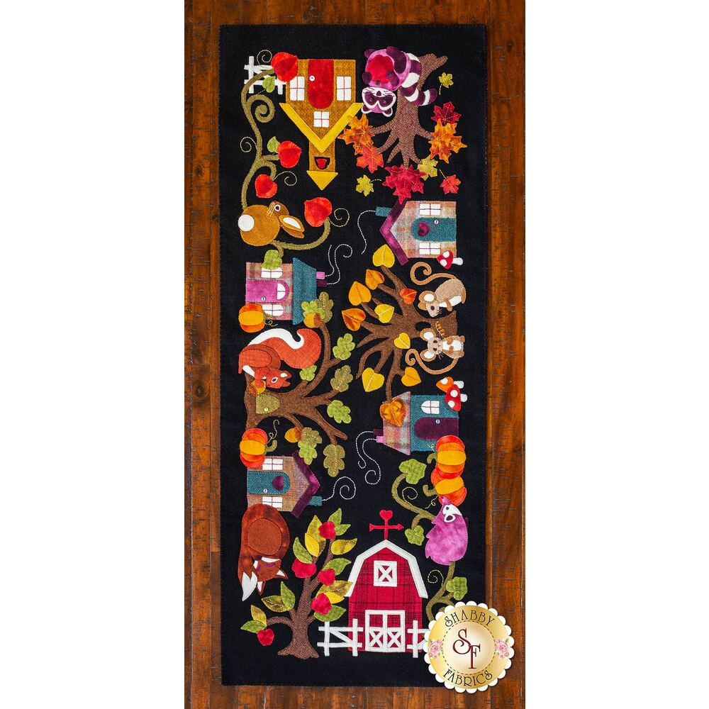 Colorful wool applique table runner featuring cute woodland animals, cozy houses, barn and trees.