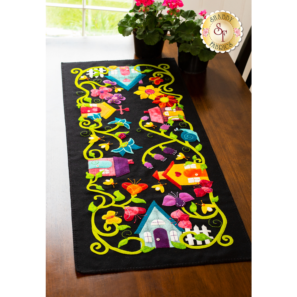 Bright wool applique table runner featuring a neighborhood of houses entangled with flowering vines.