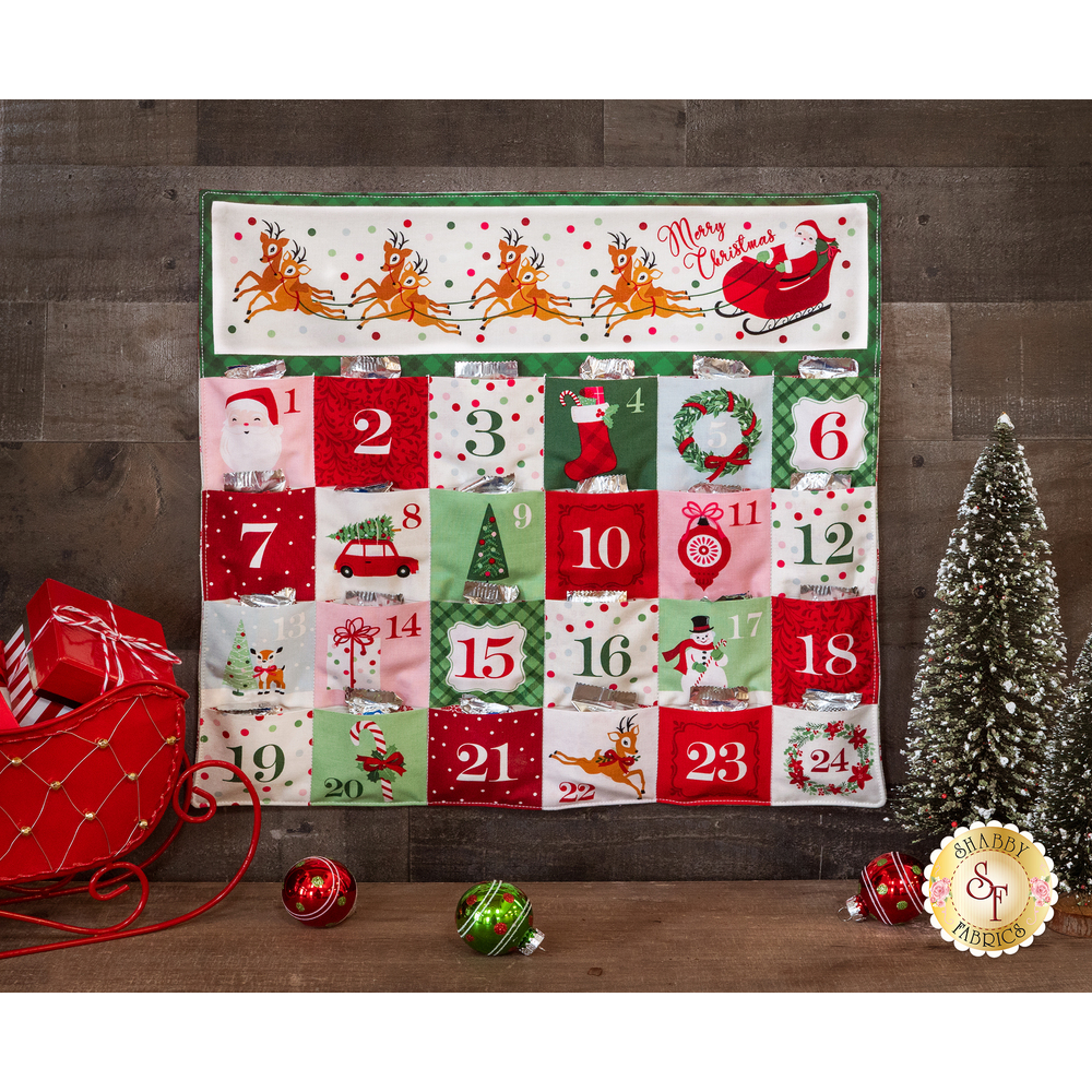 The Merry & Bright Advent Calendar in cream, displayed behind ornaments and a small Christmas tree