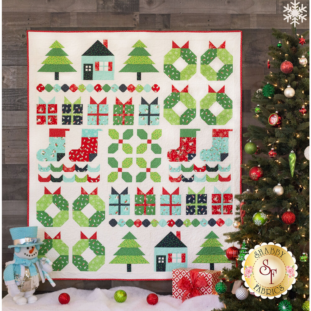 Styled Image of the North Pole Sampler Sew Along Quilt Hung On Wall | Shabby Fabrics