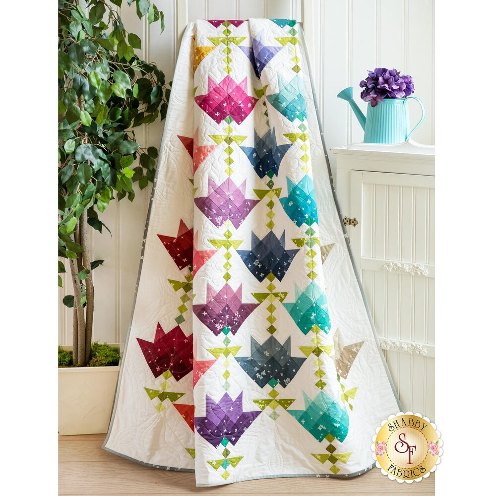 The Ombre Flower Bouquet Quilt draped next to a cabinet | Shabby Fabrics