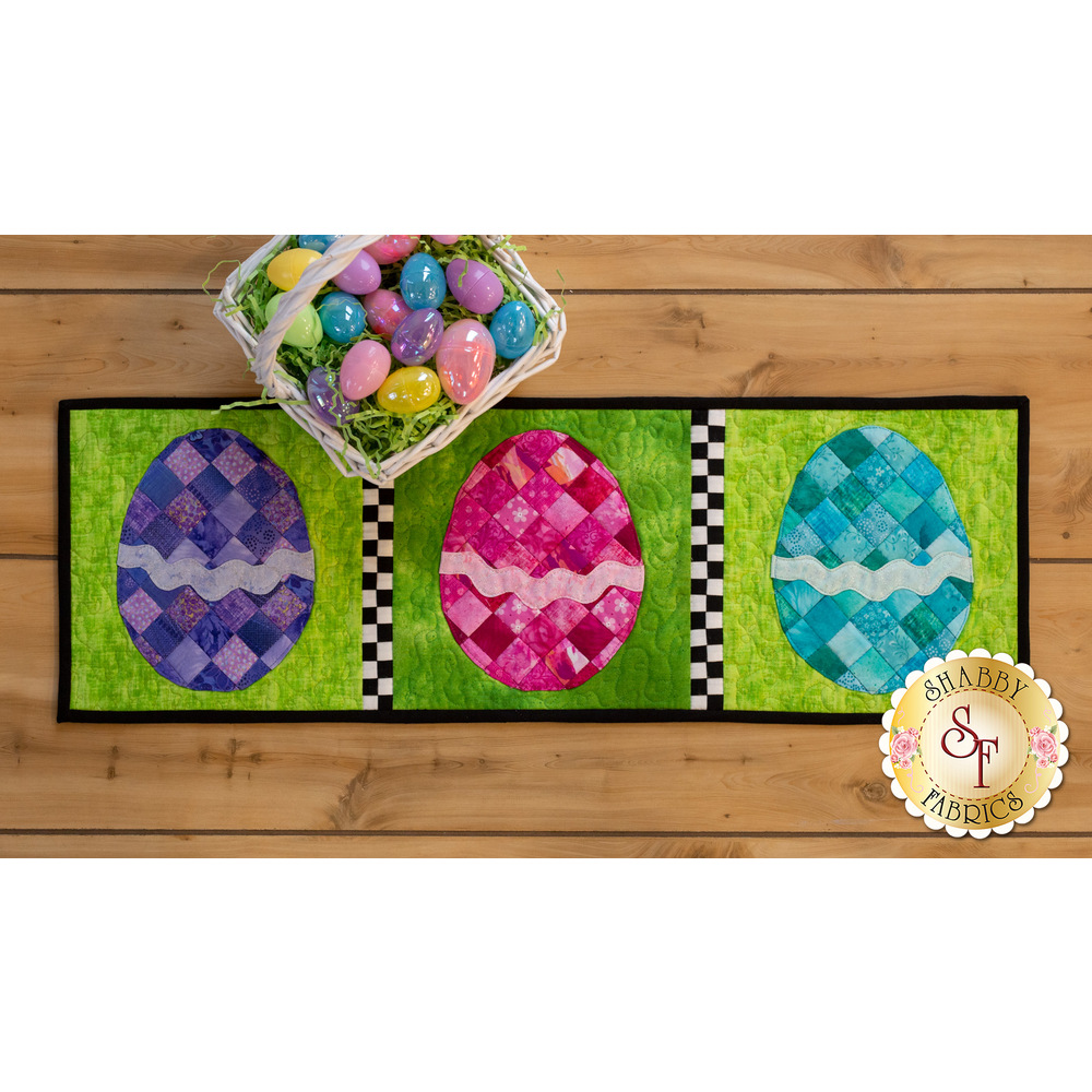 Table runner featuring purple, pink, and blue patchwork eggs on green textured background.