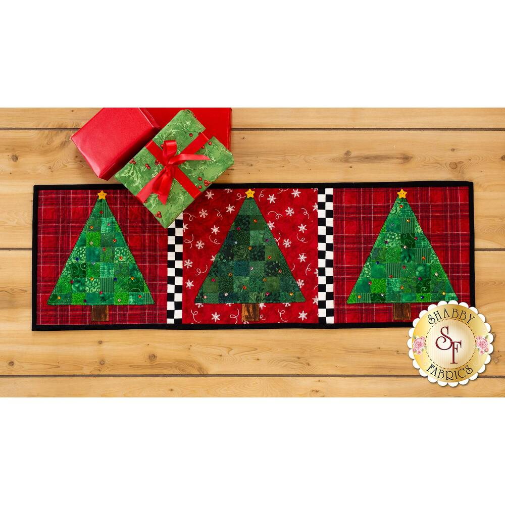 Green patchwork trees with rhinestones on red print backgrounds with checkerboard dividers.