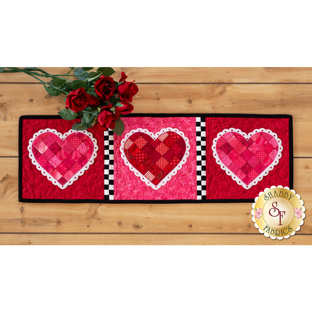 Table runner featuring red and pink patchwork hearts with mock lace applique borders.