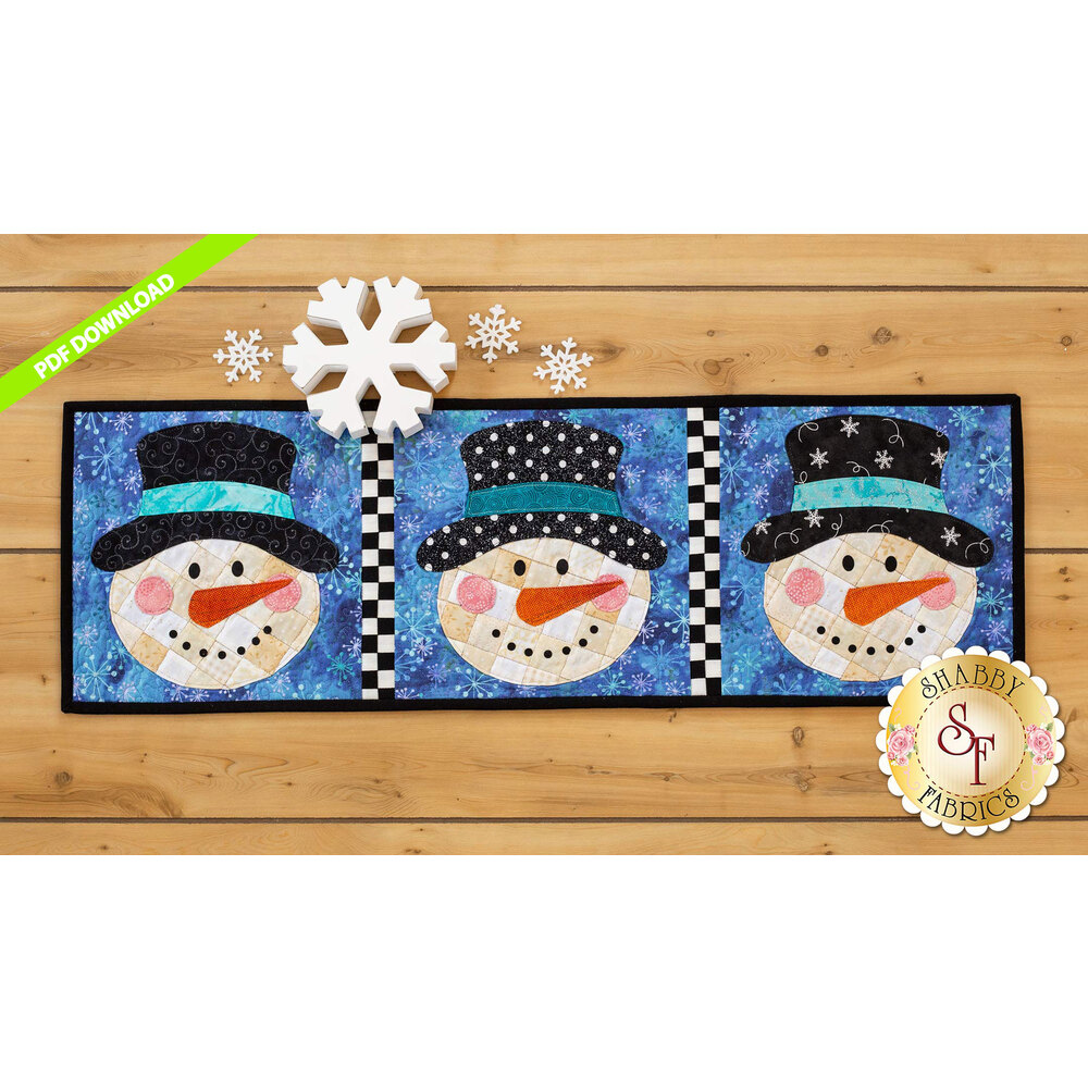 Table runner featuring three smiling snowmen with different hats on a blue backgrounds.