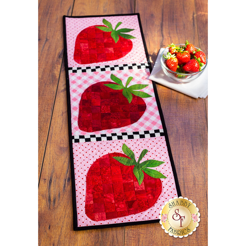 Table runner featuring three red patchwork strawberries on pink print backgrounds.
