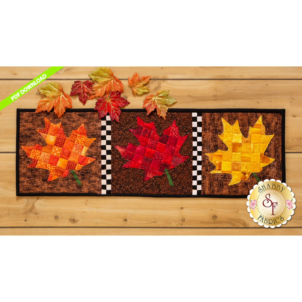 Table runner featuring orange, red, and yellow patchwork maple leaves on brown print backgrounds.