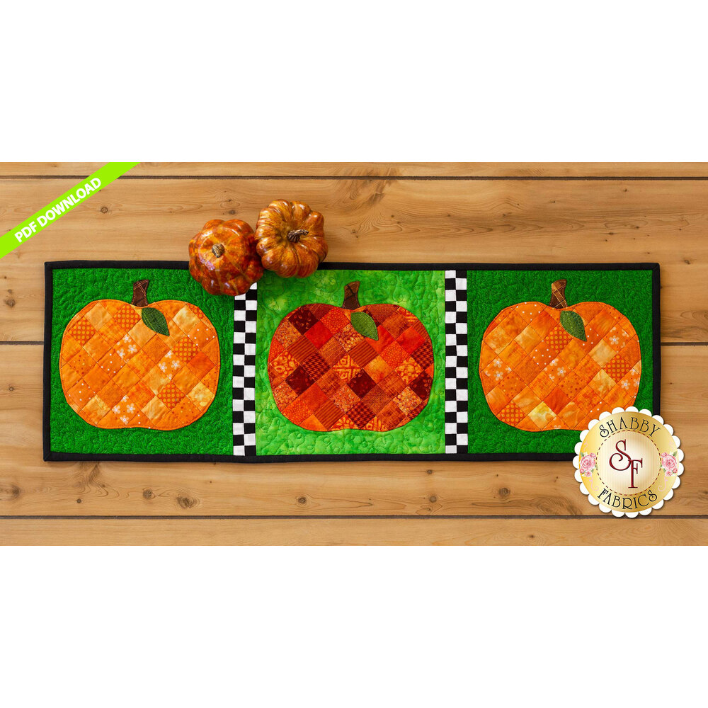Table runner featuring orange patchwork pumpkins on green print backgrounds.