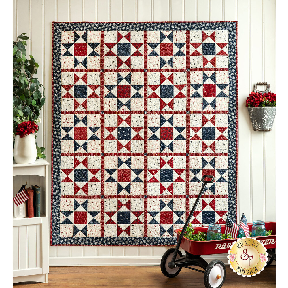 A beautiful red, white, and blue patriotic quilt hung from a wall