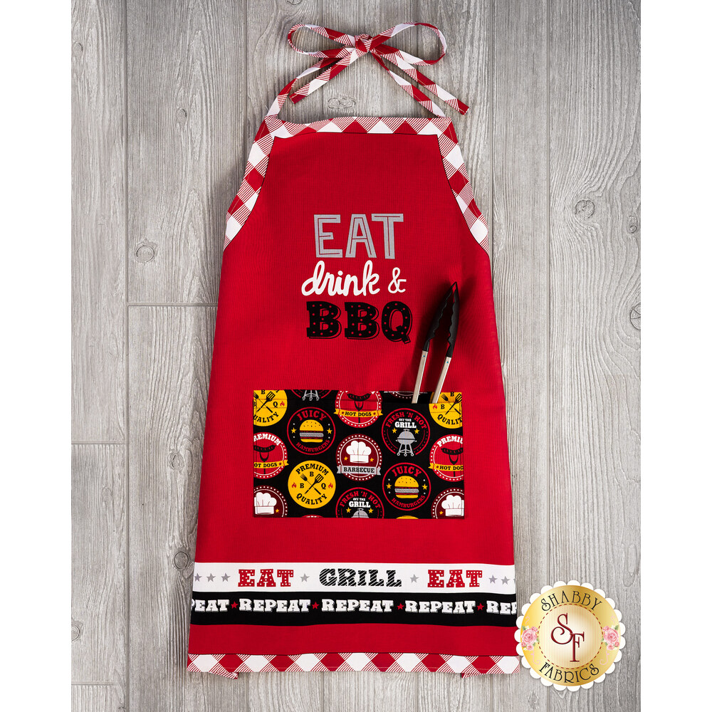 The adorable Peace, Love & BBQ Apron on wood background