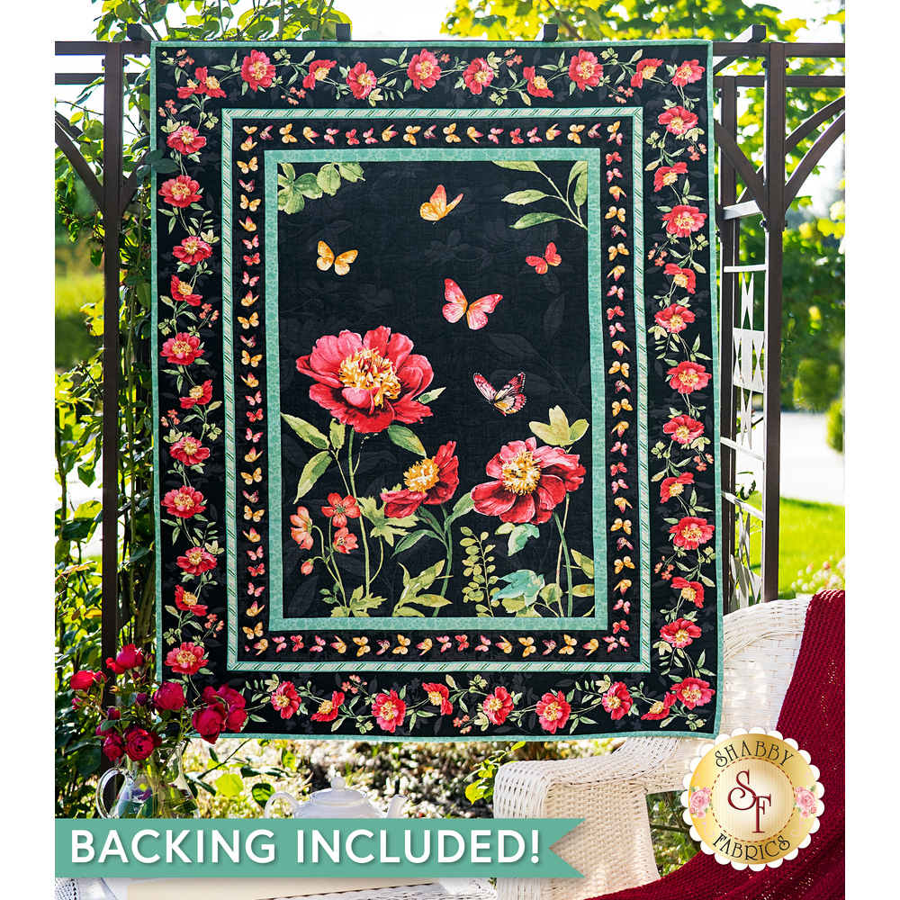 A beautiful black, pink, and teal quilt hanging outdoors