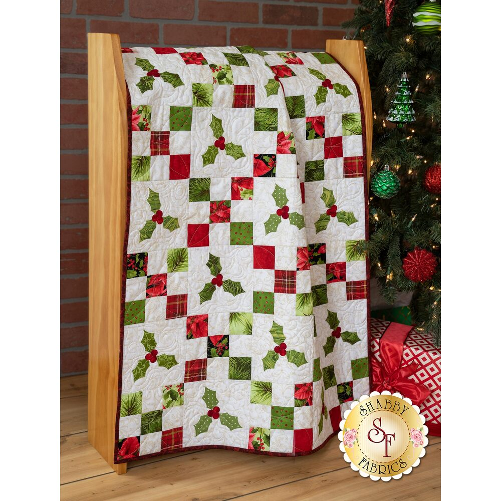 The Poinsettia & Pine Irish Chain Applique Quilt draped over a wood bench