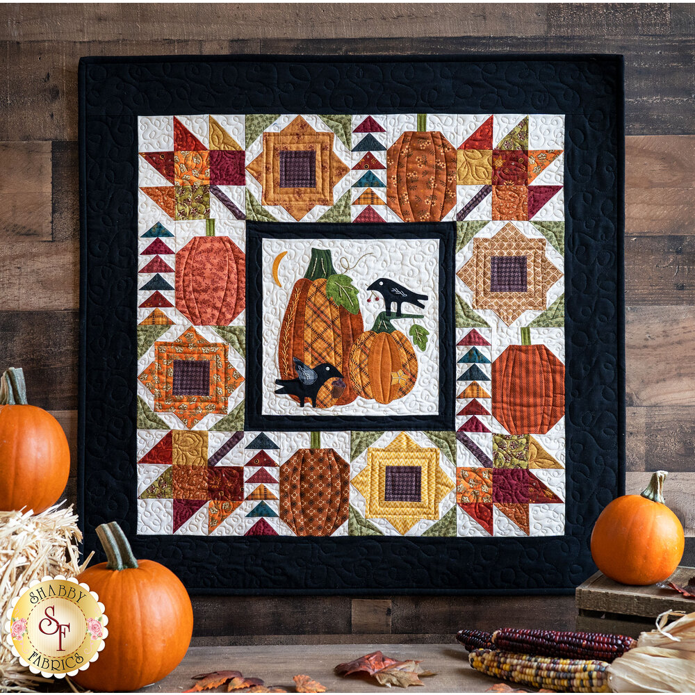 The Pumpkin Patch Wall Hanging displayed in front of pumpkins and hay