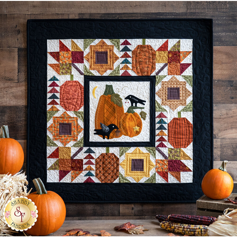 The wool Pumpkin Patch Wall Hanging displayed in front of pumpkins and hay