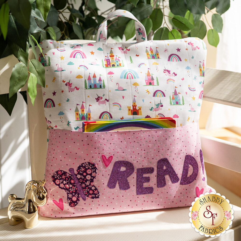 The adorable Unicorn Kingdom Reading Pillow displayed on a chair