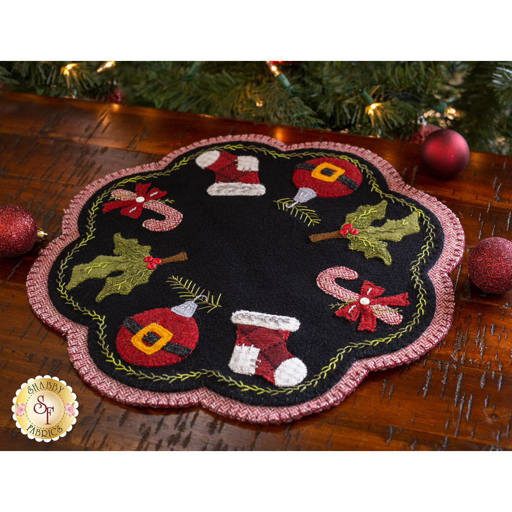 The finished Santa Baby Penny Mat displayed on a wood table | Shabby Fabrics