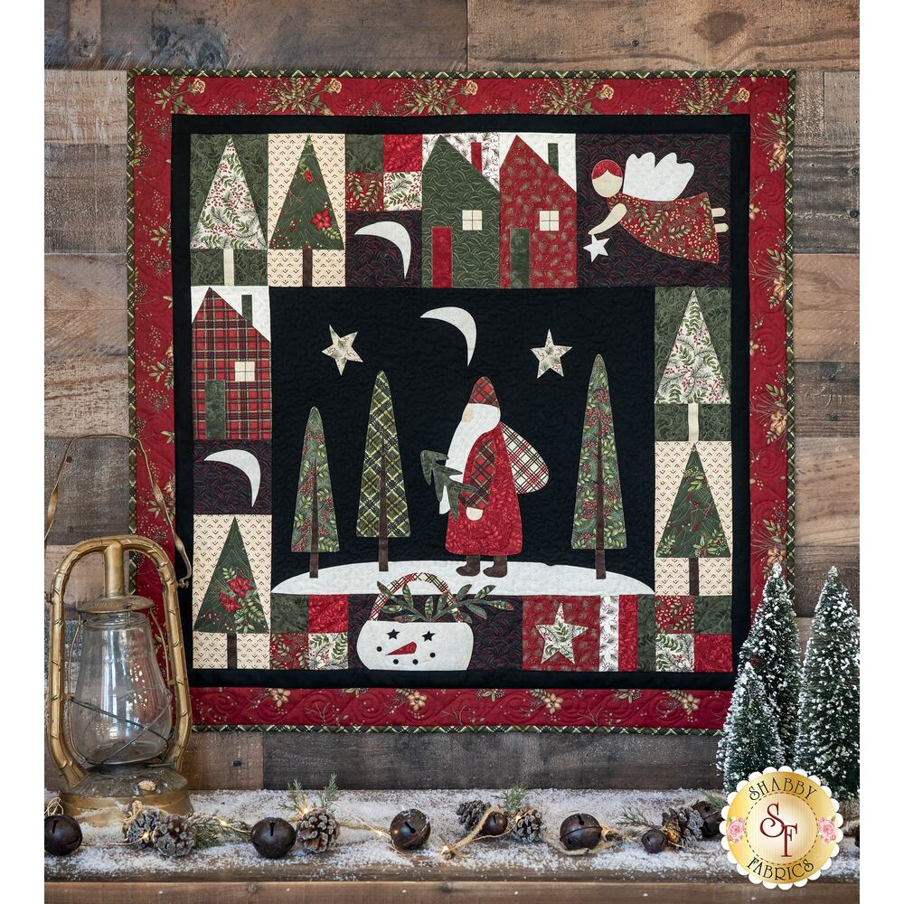 Christmas quilt showing an angel and Santa Claus hung on a stone wall | Shabby Fabrics