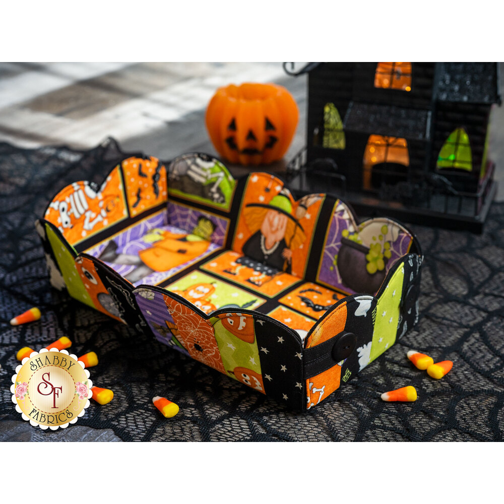 Halloween themed scalloped basket displayed on a spiderweb mat