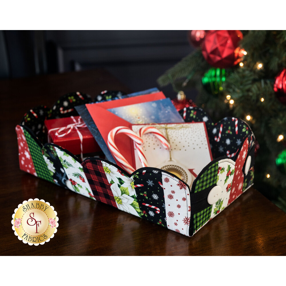 A scalloped Christmas basket full of Christmas goodies on a dark brown table