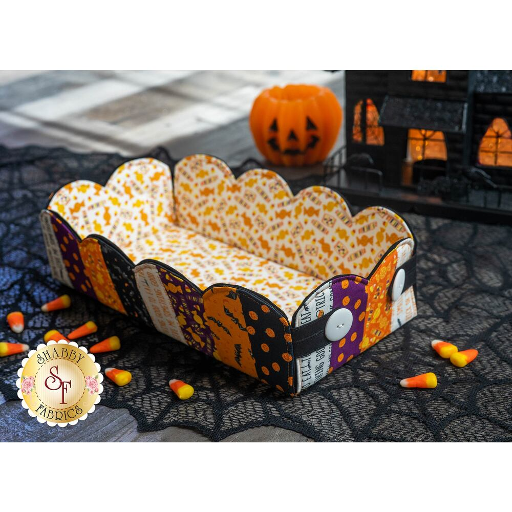 A colorful Halloween Scalloped Basket resting on a spiderweb mat with scattered candy corn