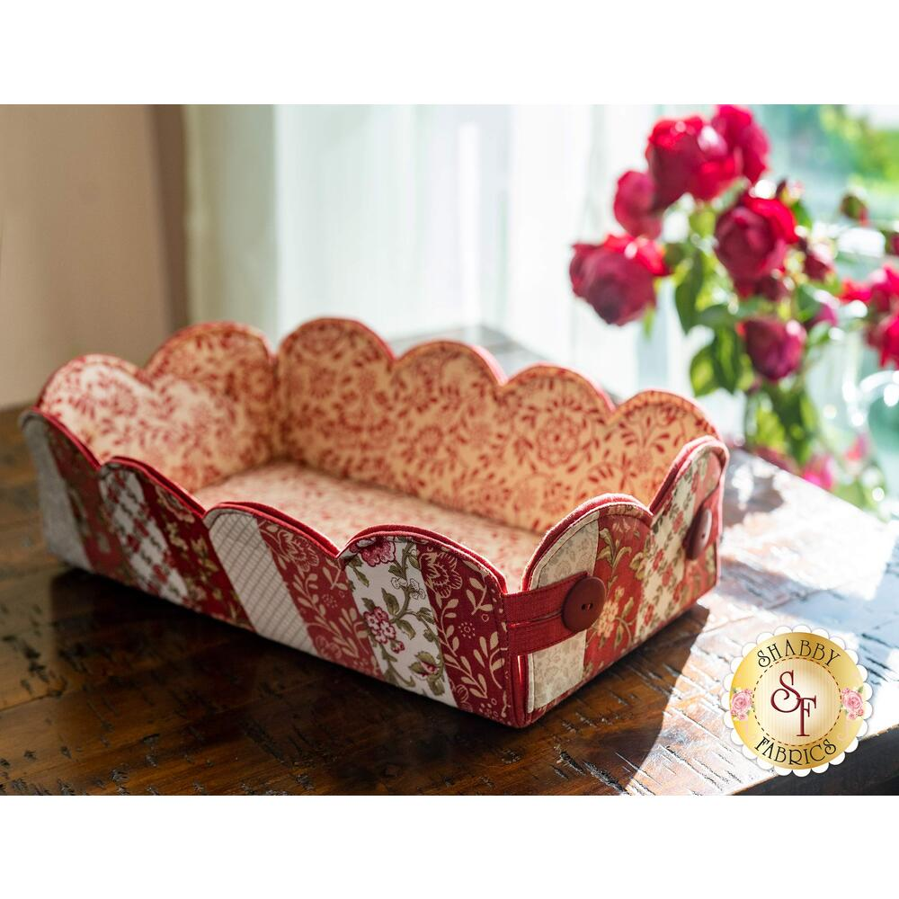 The beautiful La Rose Rouge Scalloped Basket displayed on a wood table in front of a window