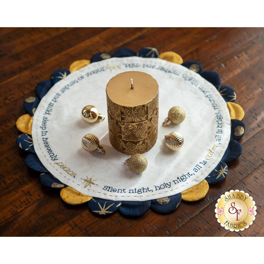 A gold candle and ornaments displayed on top of the Silent Night Scalloped Table Topper