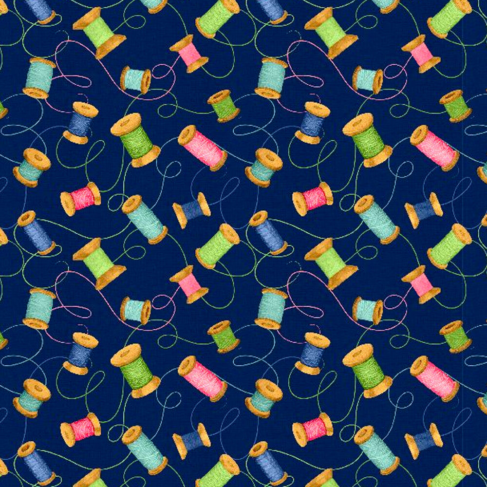 Tossed colorful spools of thread all over a blue background