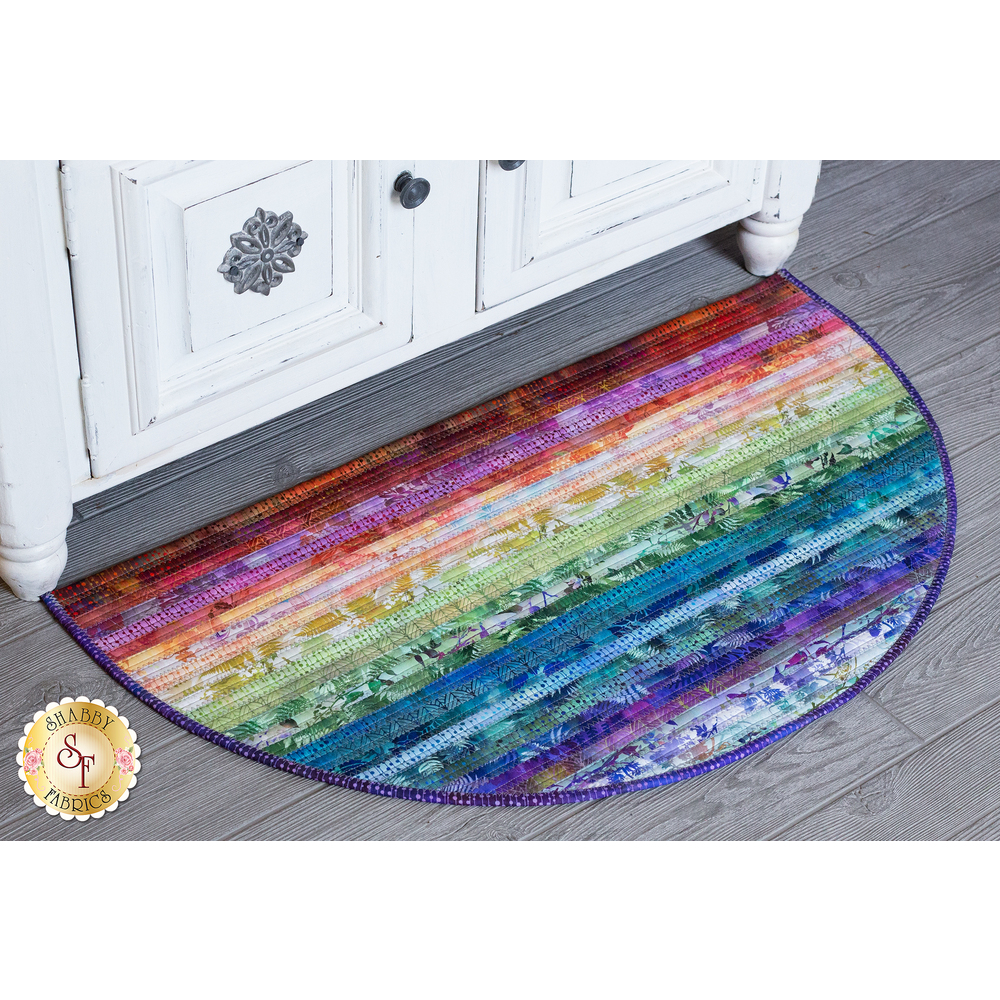 A colorful striped slice rug displayed on a grey hard wood floor | Shabby Fabrics