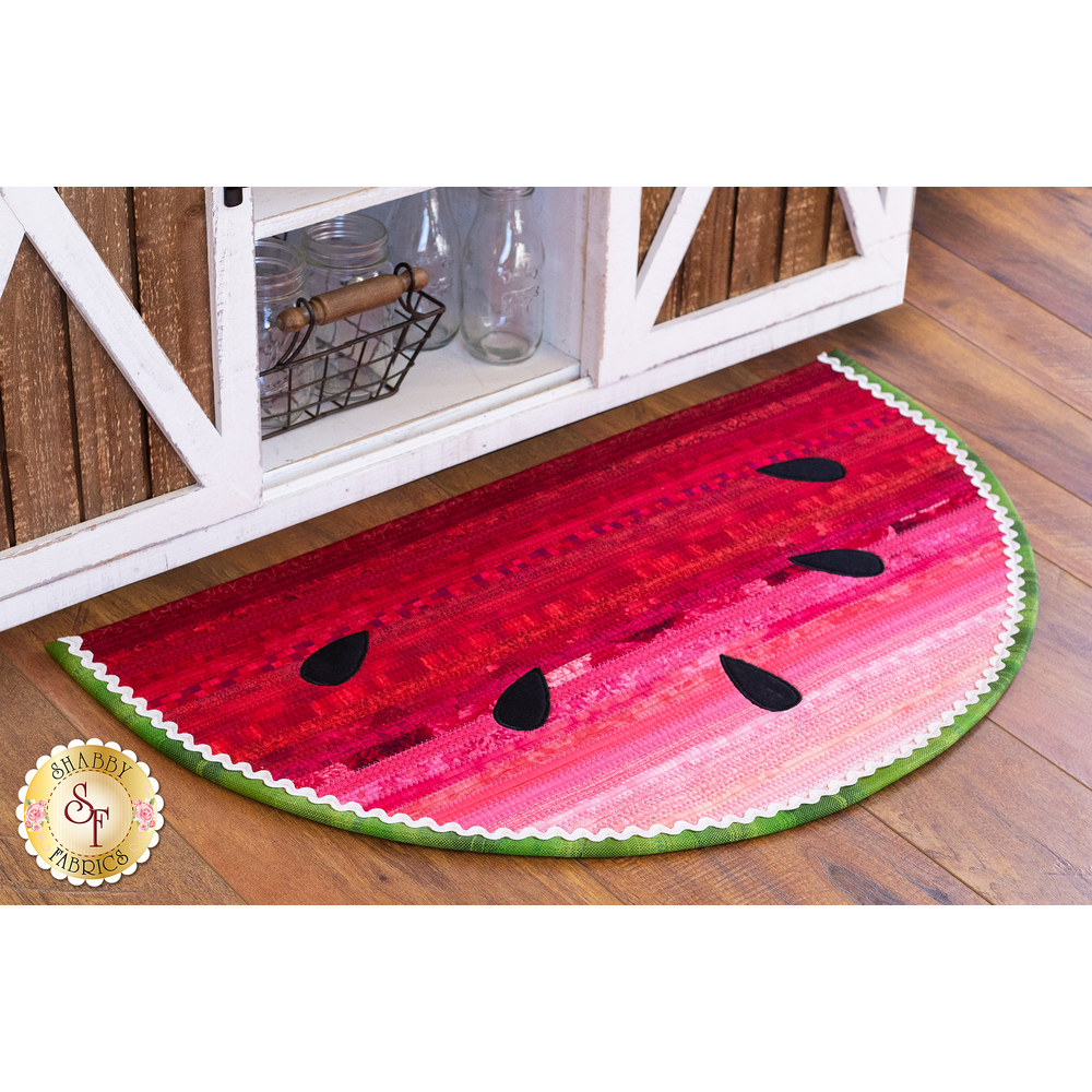 A half circle watermelon rug displayed on a wood floor | Shabby Fabrics