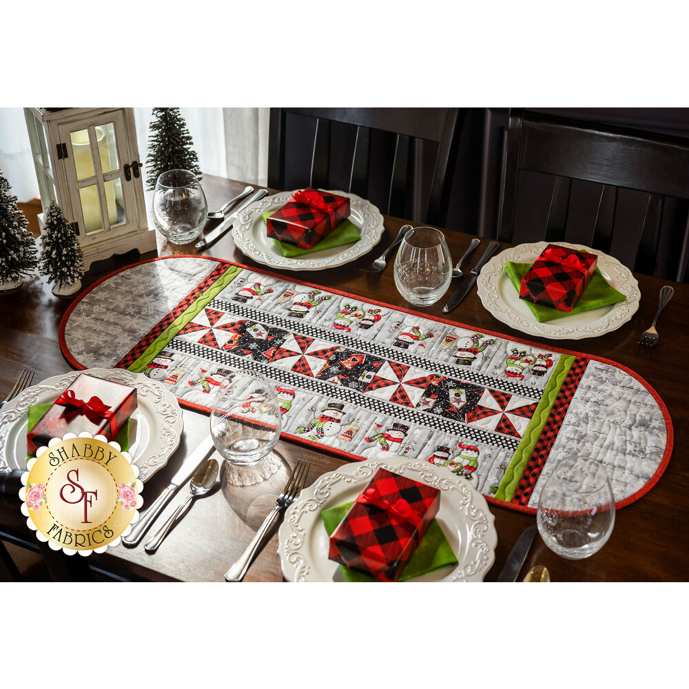 A rounded Christmas themed table runner in the center of a set dining table