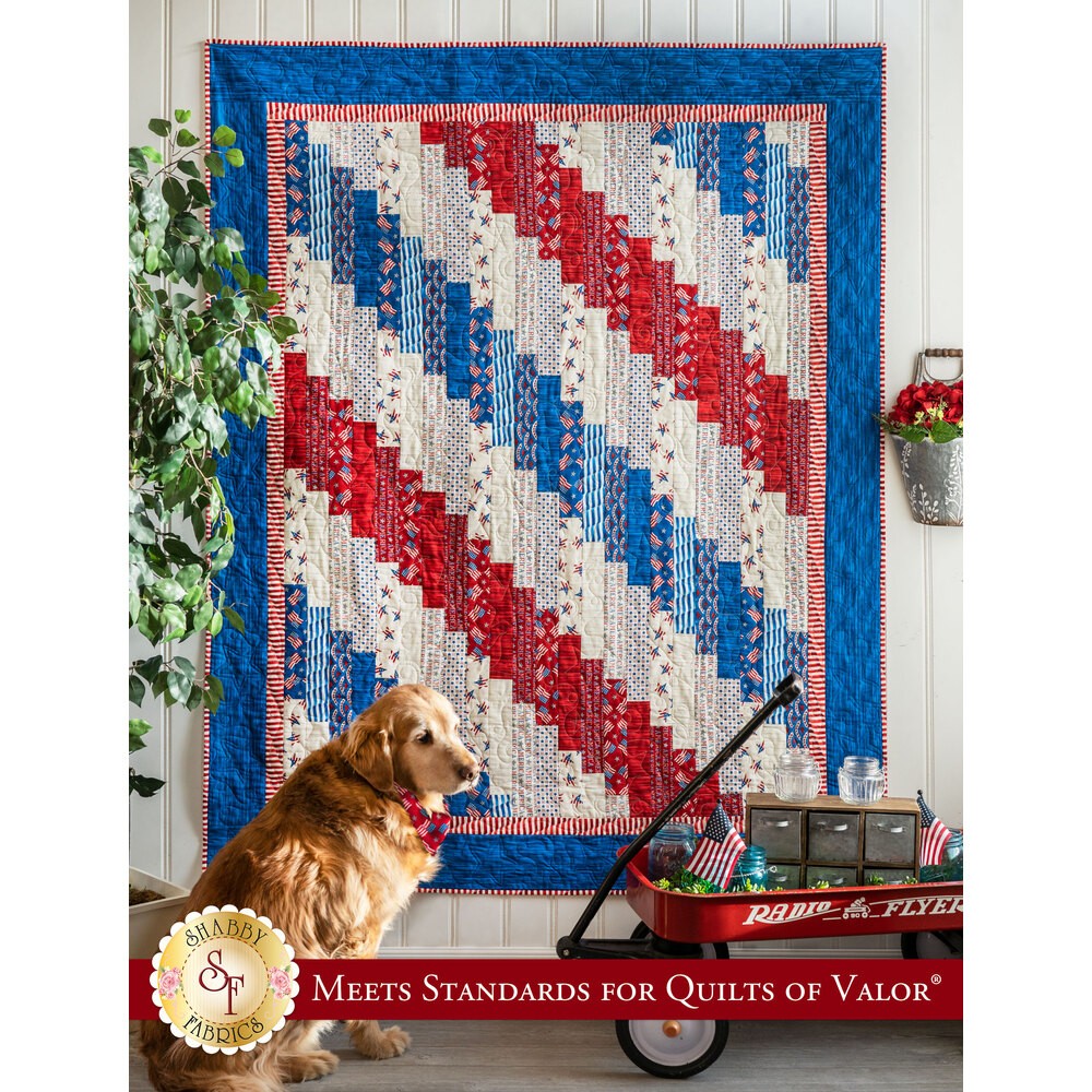A beautiful red, white, and blue quilt hung from a wall with a small red wagon nearby