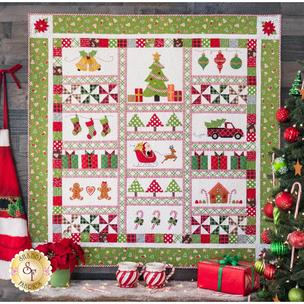 Green and white Christmas themed quilt hanging on a stone wall | Shabby Fabrics