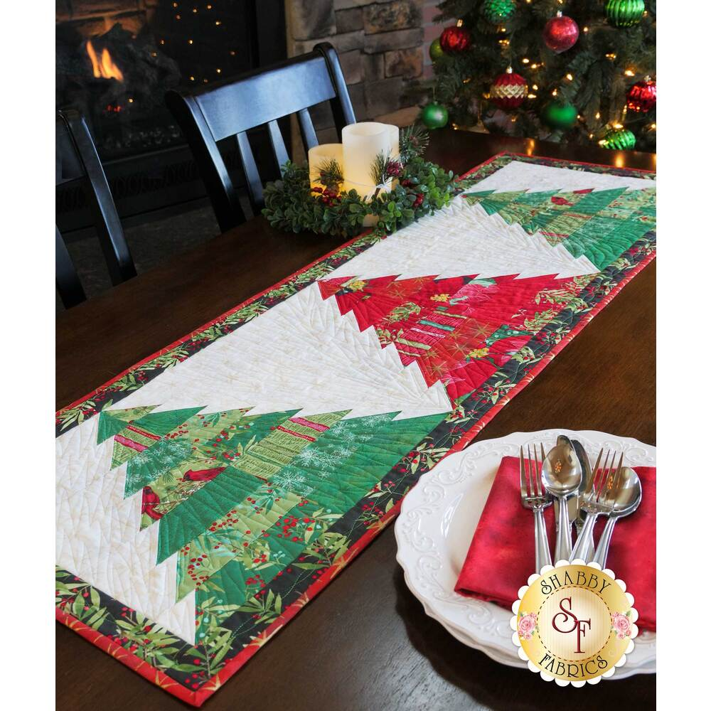 A table runner featuring 3 different colored trees on a brown wooden table