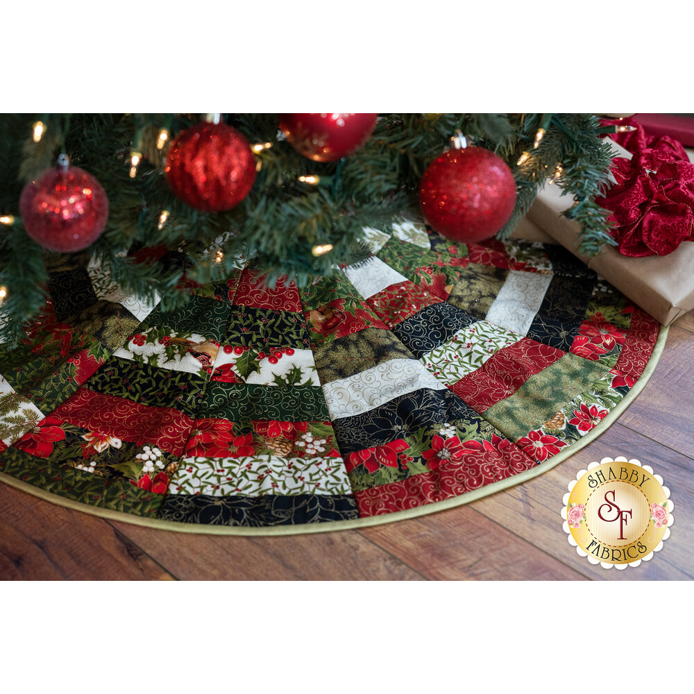 A classic Christmas colored tree skirt with metallic accents under a Christmas tree