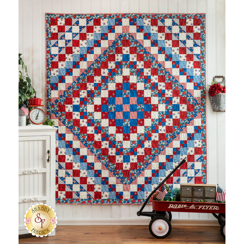 Red, white, and blue diamond patterned quilt hung from a wall