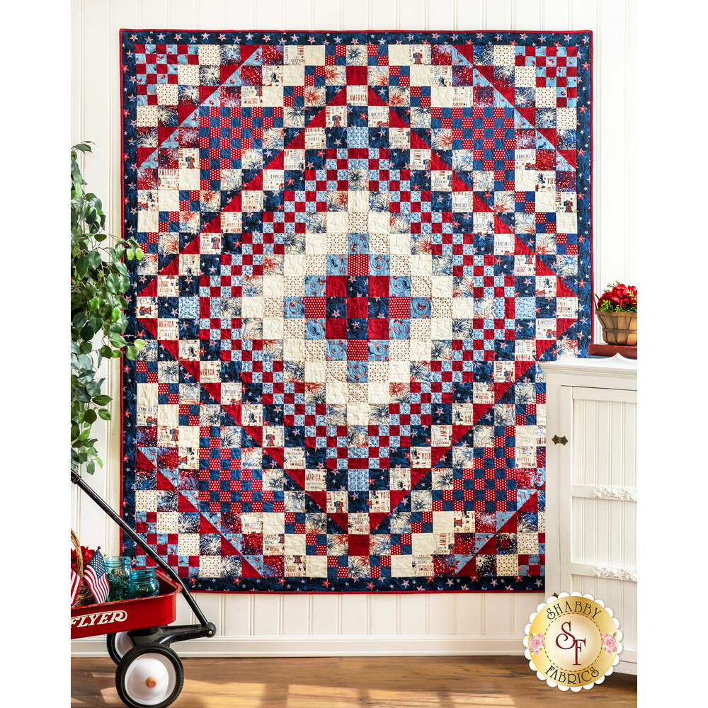 A beautiful patriotic quilt with a geometric design hanging from a wall