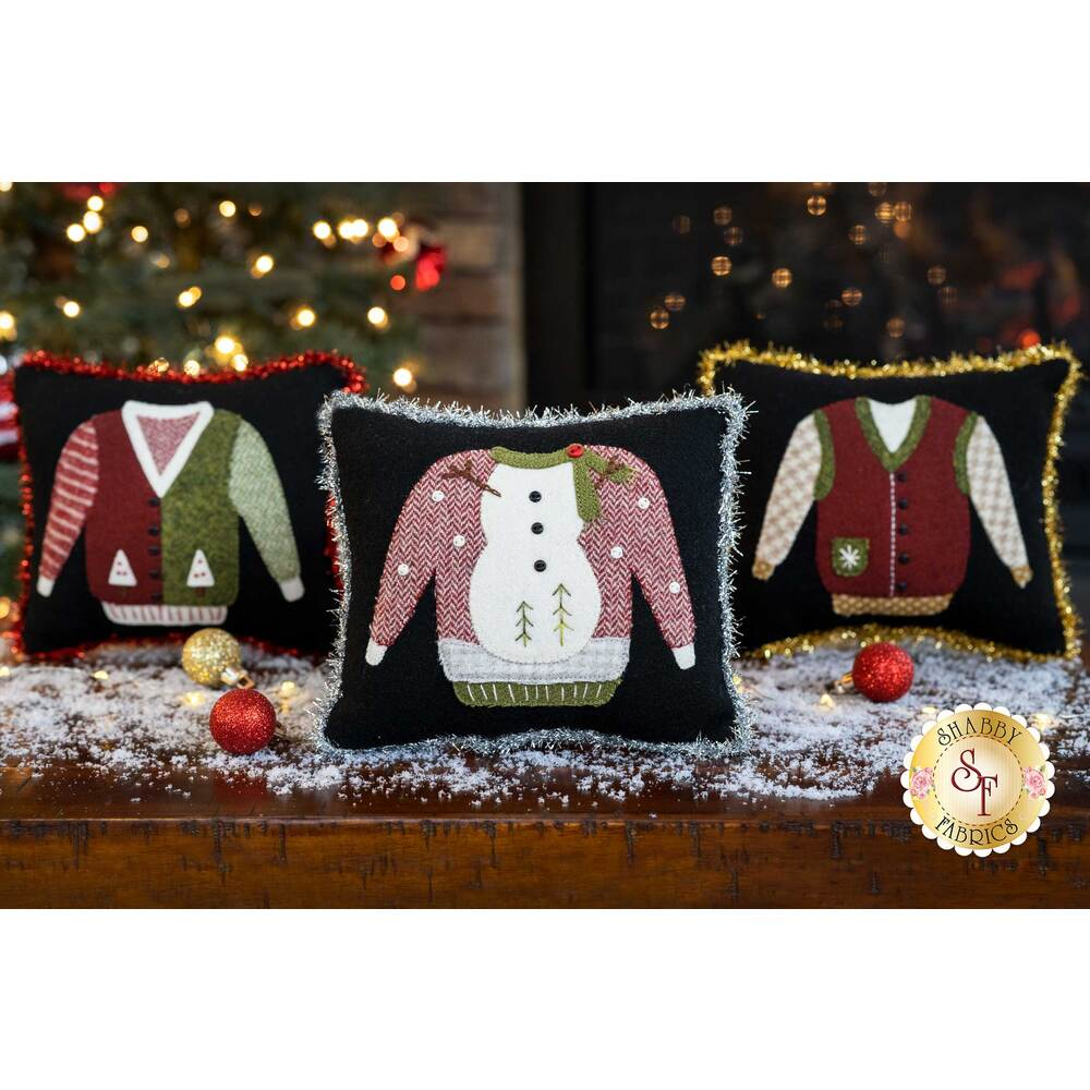 Three ugly sweater pillows displayed on a snow covered table