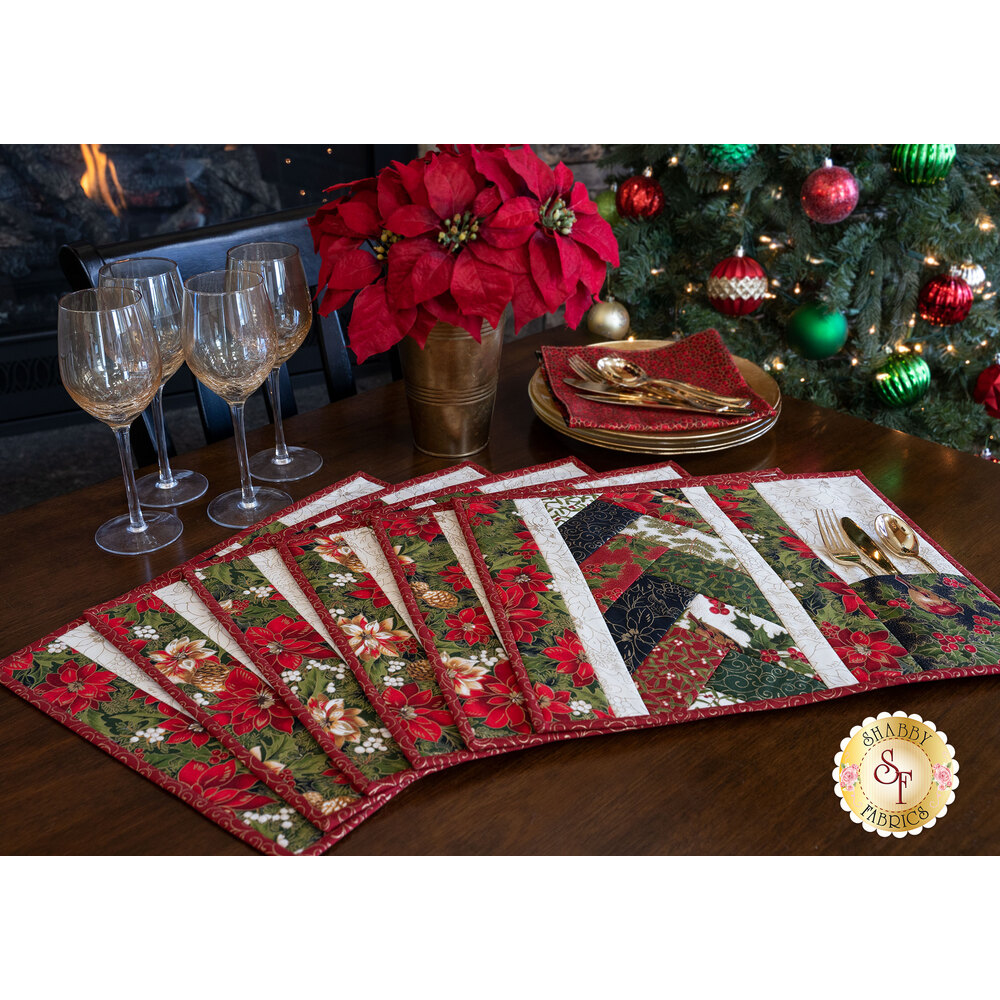 Six Christmas placemats fanned out on a wood table with wine glasses and Christmas ornaments