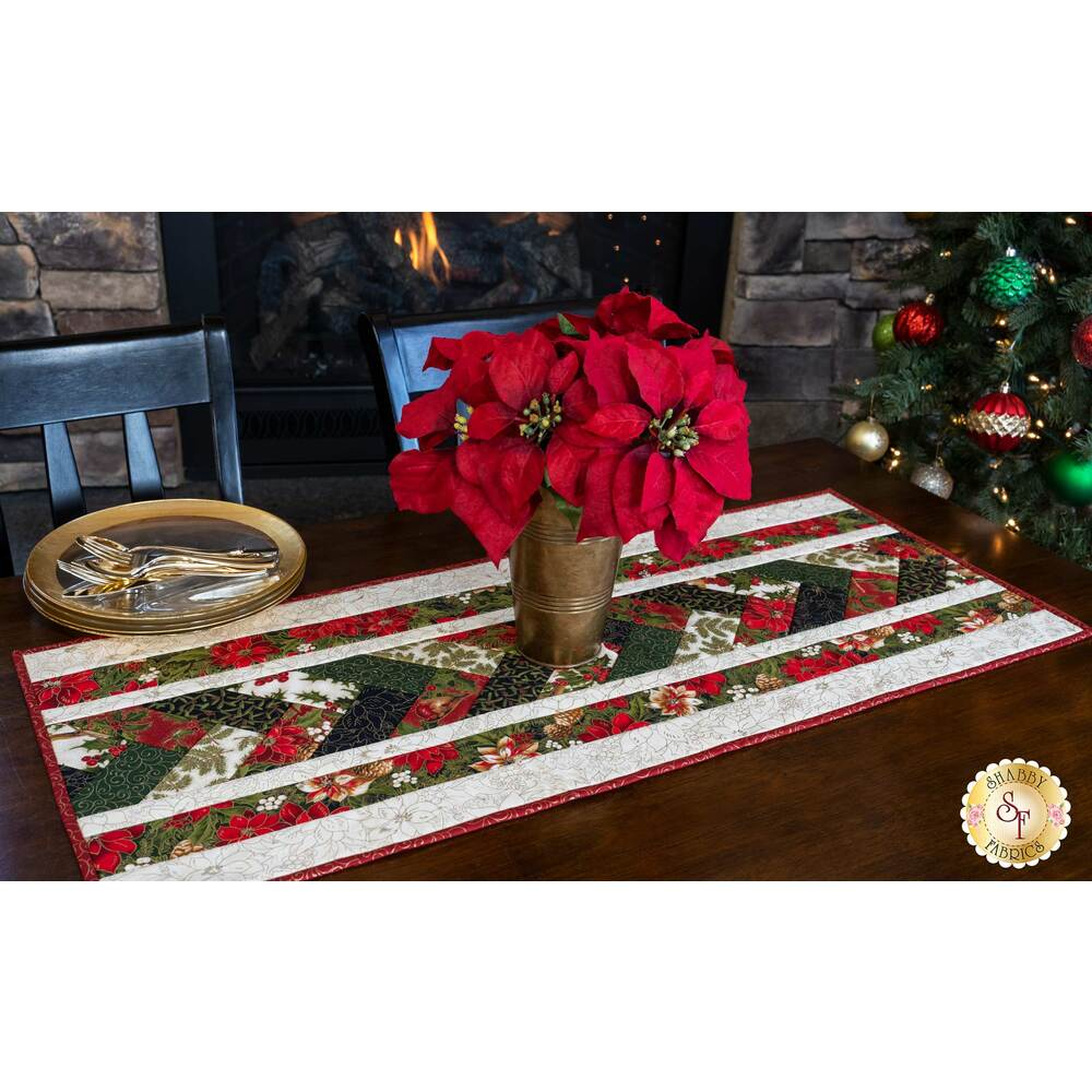 Beautiful Christmas table runner with metallic accents on a brown wooden table