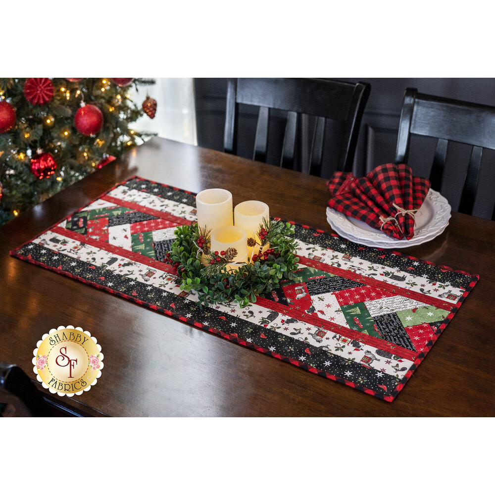 Christmas themed table runner and coordinating cloth napkin displayed on a table