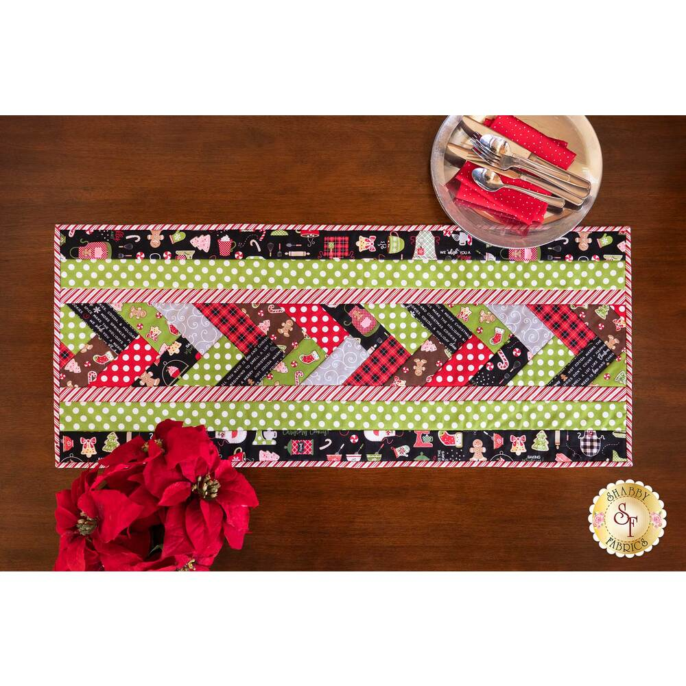 A colorful Christmas table runner on a brown table with silverware and a floral centerpiece